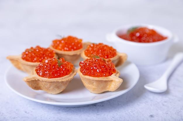 Caviar vermelho (caviar de salmão) em tortinhas. no fundo, uma tigela branca com caviar. foco seletivo, close-up.