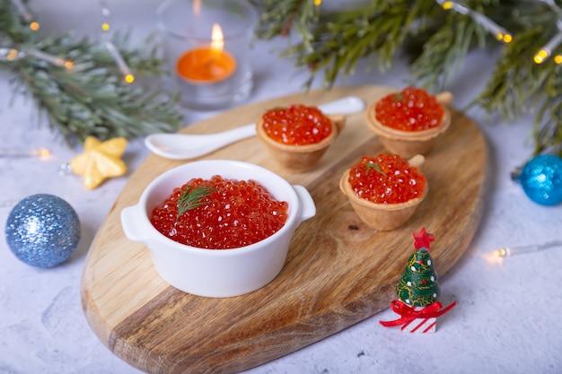 Caviar vermelho (caviar de salmão) em uma tigela branca em uma placa de madeira