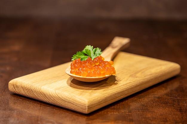 Caviar vermelho como um símbolo da riqueza. colher de madeira cheia de caviar de salmão selvagem (oncorhynchus keta) na tábua de madeira.