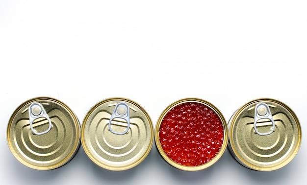 Caviar vermelho de peixe salmão. quatro latas de metal enlatadas.