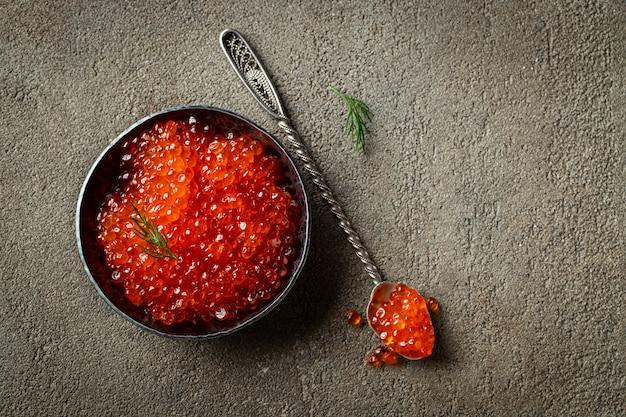 Caviar vermelho delicioso na bacia preta.