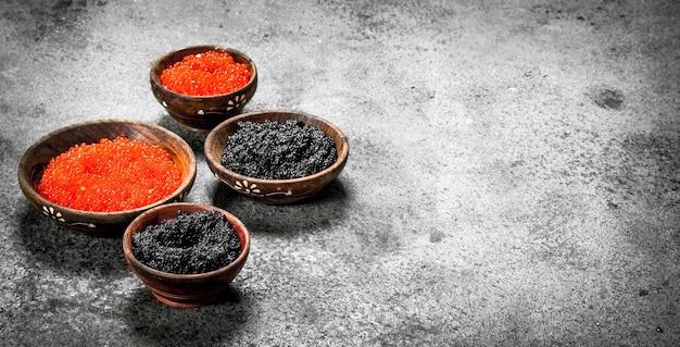 Caviar vermelho e preto em tigelas de madeira. em fundo rústico