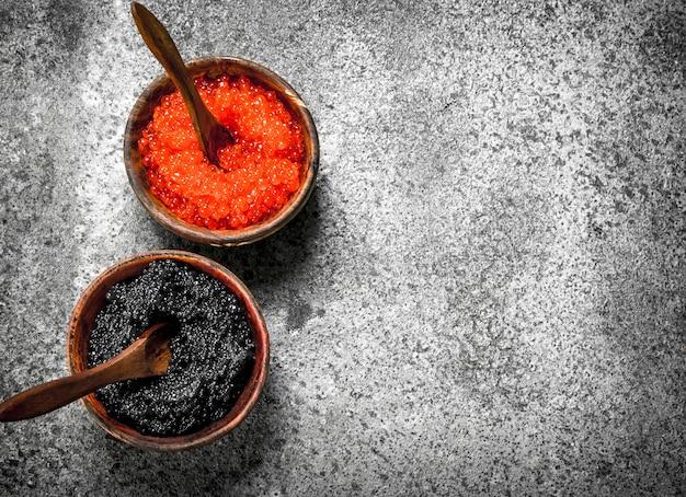 Caviar vermelho e preto em tigelas de madeira na mesa rústica.