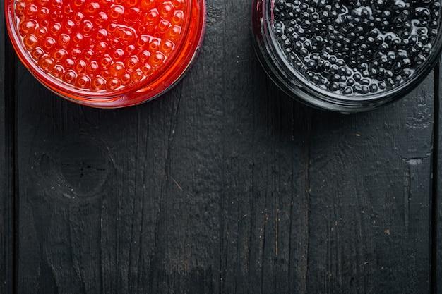 Caviar vermelho e preto em uma tigela de vidro, no fundo preto da mesa de madeira, vista de cima plana, com espaço de cópia para o texto