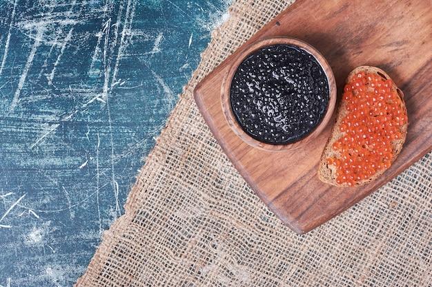 Caviar vermelho e preto na placa de madeira.