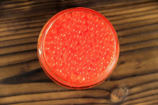 Caviar vermelho em frasco de vidro na mesa de madeira. vista do topo