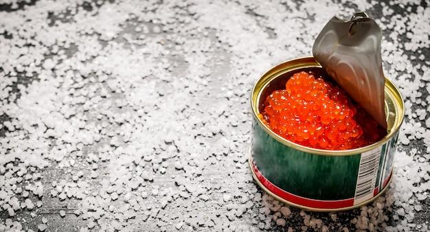 Caviar vermelho em lata de metal com sal no sal de mesa preto