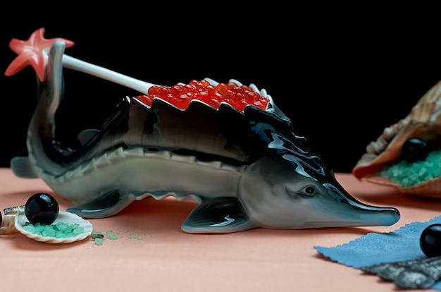 Caviar vermelho em porcelana de suporte em forma de peixe com conchas e sal marinho