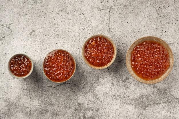 Caviar vermelho em tigelas em uma mesa de concreto cinza, cópia espaço, vista superior