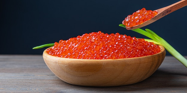 Caviar vermelho em um copo de madeira na parede de madeira com uma colher. lugar para propaganda, logotipo, etiqueta, maquete, maquete.