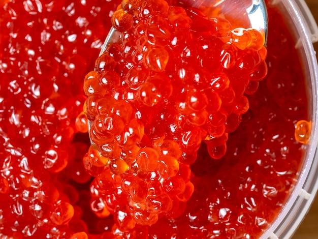 Caviar vermelho em uma colher de metal. iguaria gourmet de luxo