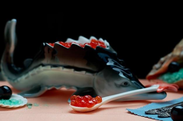 Caviar vermelho em uma colher de porcelana em primeiro plano
