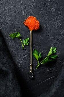 Caviar vermelho em uma colher requintada. fundo preto