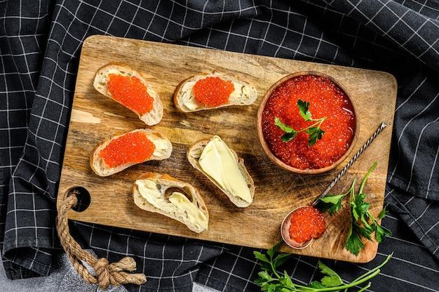 Caviar vermelho em uma tigela de madeira e sanduíches na tábua