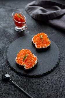Caviar vermelho em uma tigela e sanduíches de caviar em uma placa de pedra preta. em um fundo estrutural preto