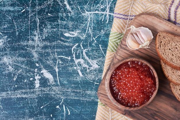 Caviar vermelho na placa de madeira com fatias de pão.