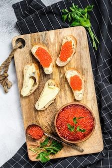 Caviar vermelho na tigela de madeira e sanduíches na tábua.