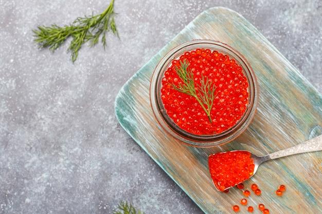 Caviar vermelho na tigela de vidro e em uma colher, vista superior