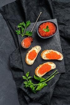 Caviar vermelho na tigela e sanduíches na placa de pedra