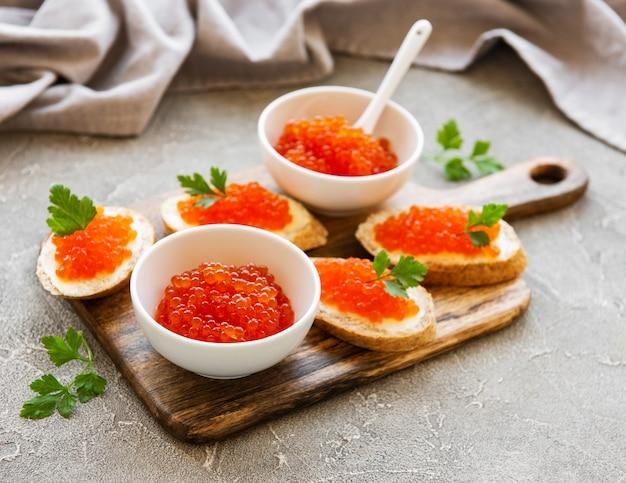 Caviar vermelho na tigela e sanduíches