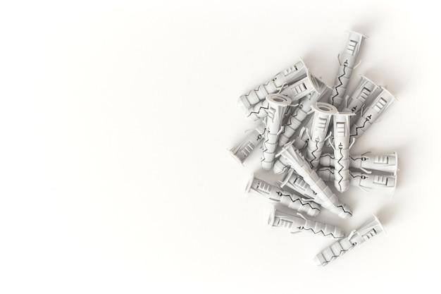 Cavilhas de plástico isoladas no fundo branco. plugue de parede, âncora de parafuso, ferramentas de construção.