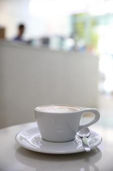 Ccappuccino ou café latte art feito com leite na mesa branca de uma cafeteria