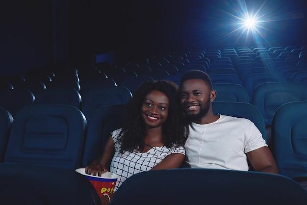 Ccouple de africanos assistindo filme engraçado
