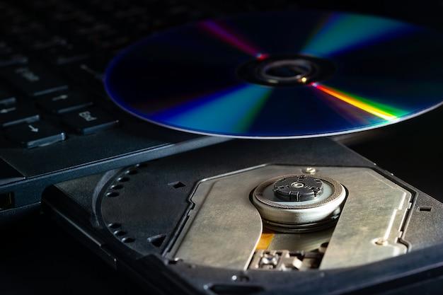 Cd no notebook computador cd rom na escuridão. avanços tecnológicos nos sistemas de registro de dados de computadores.