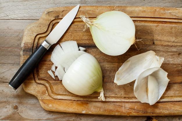 Cebola branca crua fresca cortada na placa de cozimento
