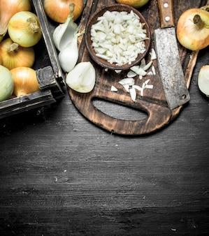 Cebola cortada em uma placa de corte com uma velha machadinha. no quadro negro.