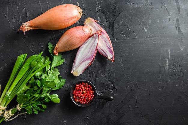 Cebola, eschalote ou cebolinha cebolas maduras cruas com verduras e pimenta rosa cortada e cortada ao meio fundo de concreto preto texturizado fundo vista superior espaço para texto