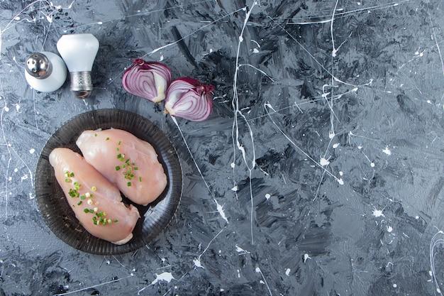 Cebola fatiada e peito de frango em um prato, no fundo de mármore.
