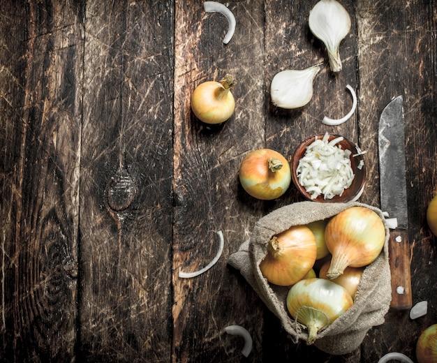 Cebola fresca fatiada com velha machadinha. sobre um fundo de madeira.