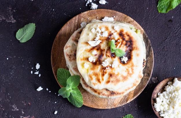 Cebola, hortelã e queijo pequenos pães servidos em uma placa de madeira. gozleme.