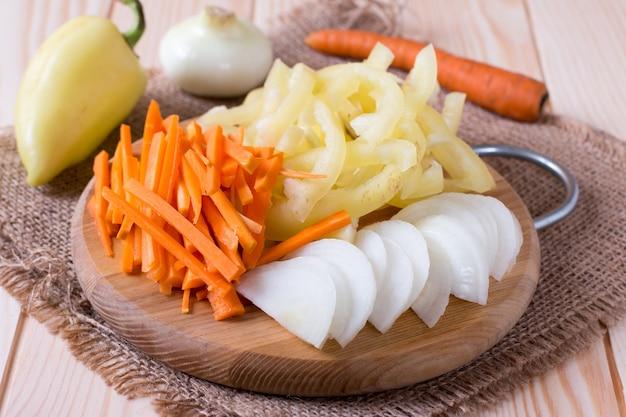 Cebola picada, cenoura e pimentão na tábua