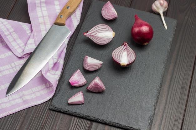 Cebola picada e uma cebola inteira na tábua. faca no guardanapo. fundo de madeira escuro. vista do topo