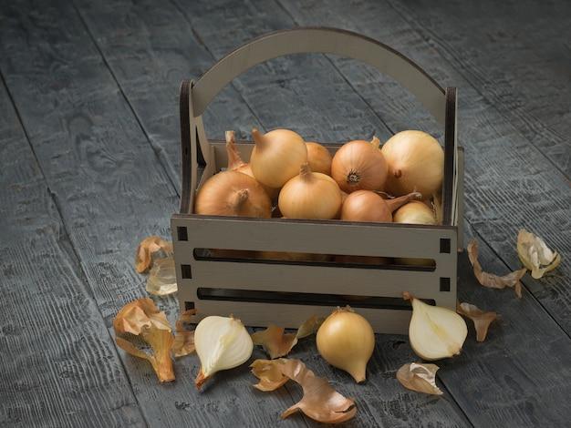Cebola recém colhida em uma caixa de madeira e sobre uma mesa de madeira.