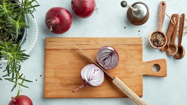 Cebola roxa cortada ao meio em uma tábua de cozinha de madeira, vista superior
