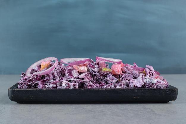 Cebola roxa picada e salada de repolho em uma travessa na mesa de concreto.