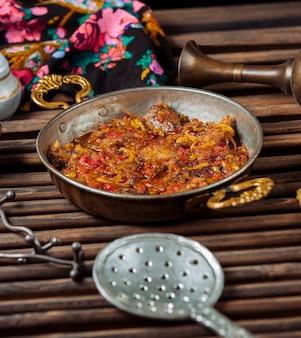 Cebola, tomate com pedaços de carne cozida em uma panela de cobre.
