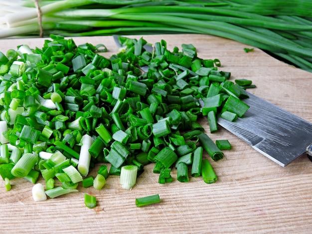 Cebola verde cortada em uma tábua e faca para cortar