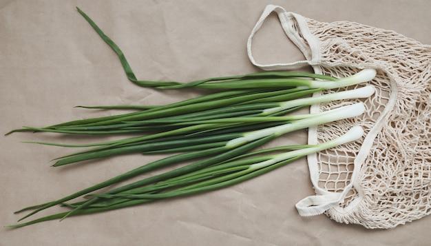 Cebola verde fresca e cebolinha em uma sacola ecológica com vista superior plana
