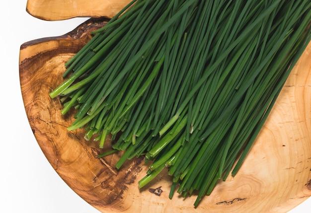 Cebola verde fresca em um prato de madeira
