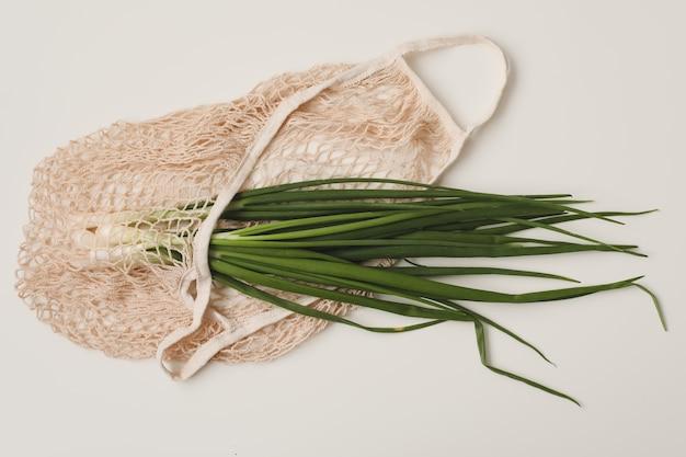 Cebola verde fresca em um saco ecológico na superfície branca