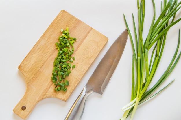 Cebola verde picada na placa de madeira, faca no fundo branco isolado