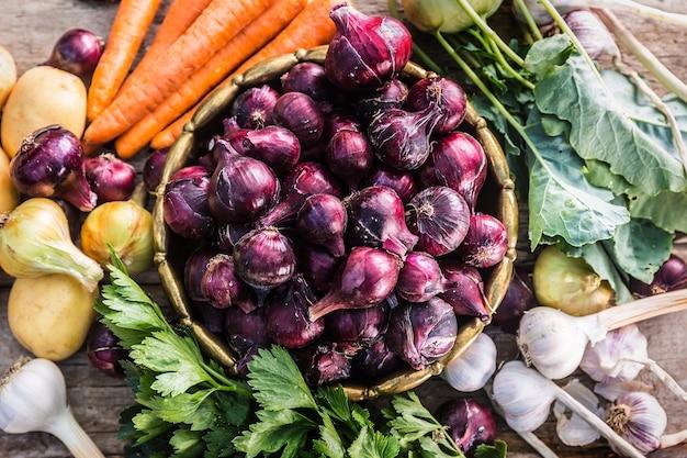 Cebola vermelha em bronze tigela alho cenoura batatas ervas aipo e couve-rábano na mesa do jardim - topo da vista. vegetais frescos saudáveis de close-up.