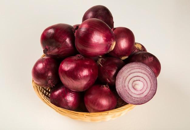 Cebola vermelha em uma cesta e uma cebola roxa cortada sobre uma mesa. cebolas
