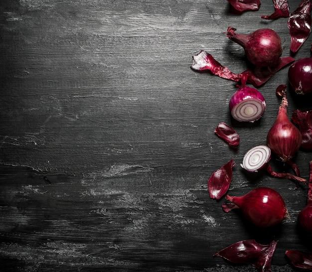 Cebola vermelha na mesa rústica preta.