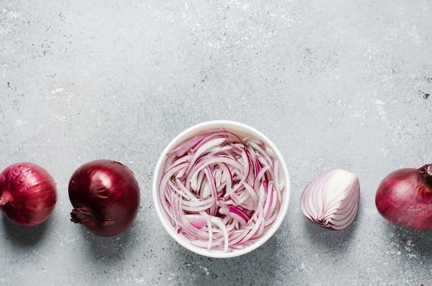 Cebola vermelha picada em conserva em vinagre em um prato branco. cebolas inteiras e fatiadas. um prato delicioso para pratos de carne e peixe. fundo cinza claro. vista superior plana
