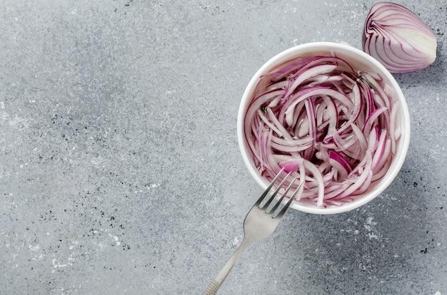 Cebola vermelha picada em conserva em vinagre em um prato branco. um prato delicioso para pratos de carne e peixe. fundo cinza claro. vista superior plana